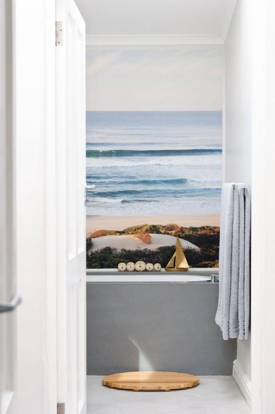 un piccolo bagno minimalista con una vasca grigia e una carta da parati con vista sull'oceano e una stuoia di legno