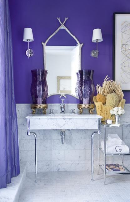 un bagno in piastrelle di marmo e viola con spugne e coralli, con uno specchio accattivante e grandi lanterne viola
