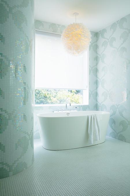 un bagno ispirato all'oceano completamente rivestito con tessere di mosaico color acqua che mostrano motivi più una soffice lampada a sospensione