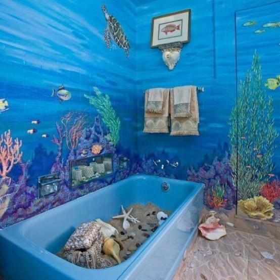un bagno super luminoso con una vasca blu con sabbia e stelle marine più conchiglie e murales ispirati ai coean