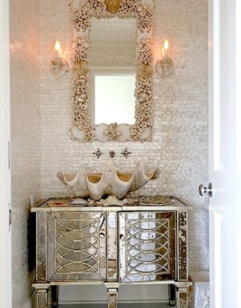 un bagno neutro con una vanità glam scintillante, uno specchio incorniciato da stelle marine e conchiglie e un lavandino gigante