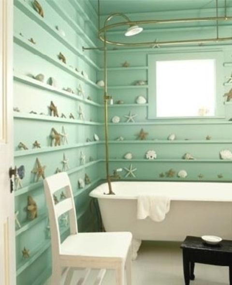 un bagno color acqua con molte sporgenze lungo le pareti e stelle marine e conchiglie più tocchi d'oro