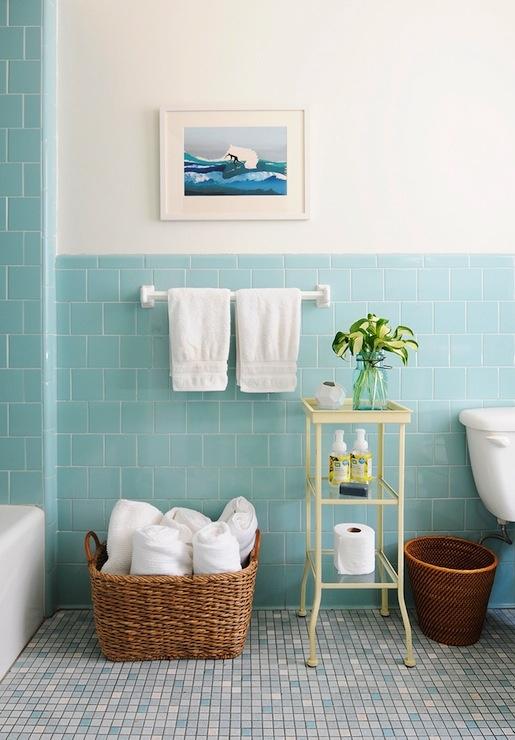 un bagno mare color acqua con pavimento a mosaico, alcuni cestini per riporre e un'etagere pastello