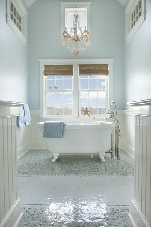 un bagno azzurro e cremoso con un pavimento a mosaico, sfumature romane intrecciate, una vasca da bagno con i piedini e un lampadario