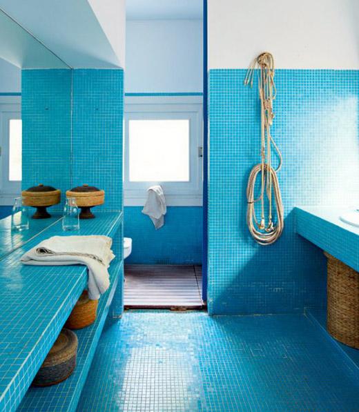 un bagno contemporaneo blu brillante con tocchi di corda, cestini e asciugamani neutri