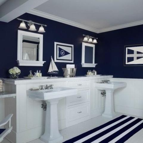 una marina nautica e un bagno bianco con strisce, specchi e decorazioni di barche e navi