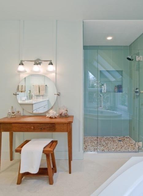 un bagno neutro sulla spiaggia con piastrelle color acqua nella doccia, un lavabo in legno più uno sgabello e alcune creature marine