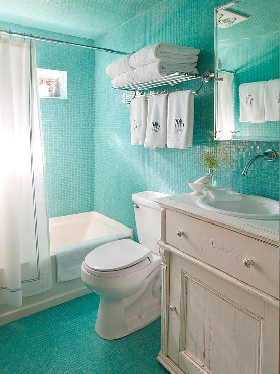 un bagno turchese brillante con tocchi di bianco, mobili color crema, asciugamani e una tenda da doccia