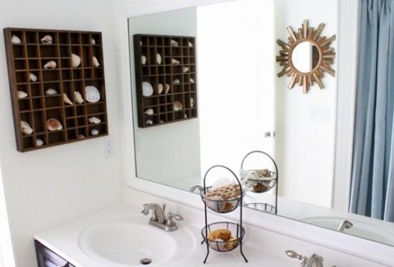 un bagno neutro con una mensola a scatola con conchiglie e stelle marine, uno specchio a raggiera e un supporto con saponi e spugne