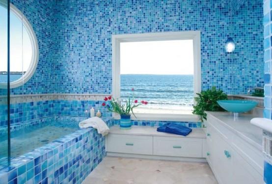 un bagno blu ispirato al mare con piastrelle a mosaico, mobili bianchi e ampie finestre con vista sull'oceano