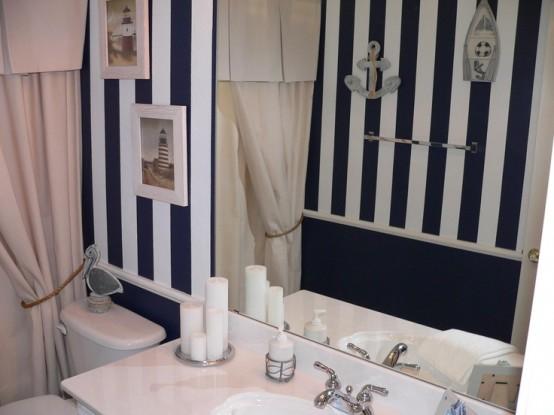 un bagno in bianco e nero con opere d'arte ispirate al mare e alcune applique sul muro