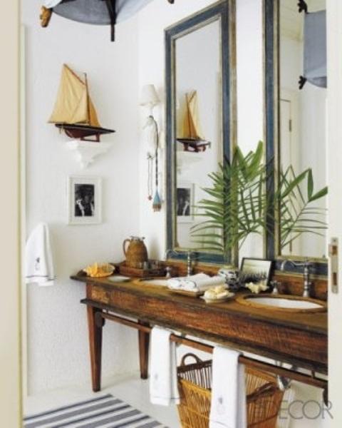 un bagno nautico con una vanità in legno vintage, specchi con cornice verde acqua, una decorazione della nave e un cestino per la conservazione