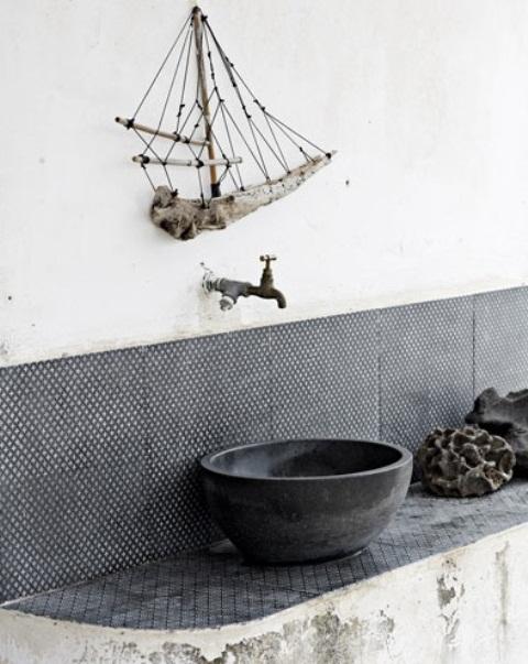 un bagno wabi-sabi con una vanità shabby chic, piastrelle bianche e nere, un lavandino di una nave di cemento e un'arte della nave di ramo