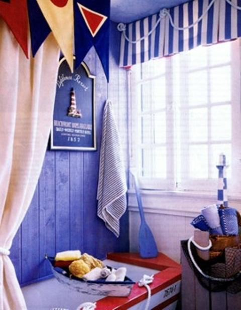 un bagno blu, rosso e bianco con una vasca da bagno a forma di barca, tende accattivanti, spugne e asciugamani per un'atmosfera più ispirata al mare