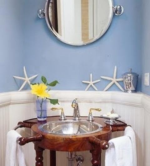 un bagno vintage blu e bianco con uno specchio rotondo e una vanità macchiata con un lavandino