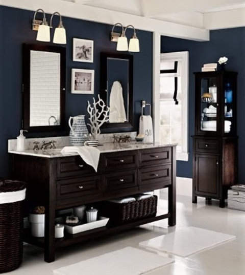 un bagno blu marino con mobili macchiati di scuro, cesti scuri e alcune superfici bianche per creare un contrasto