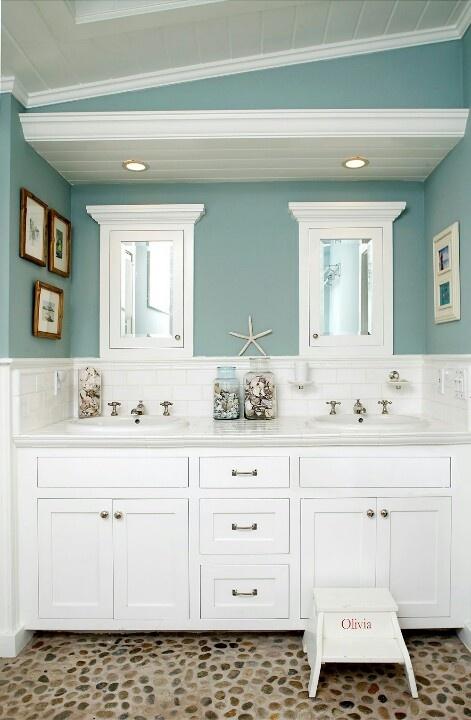 bagno blu ardesia e bianco con una grande vanità bianca, opere d'arte, stelle marine e conchiglie
