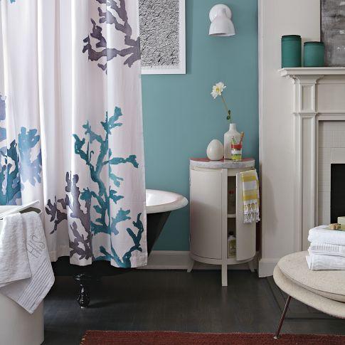 un bagno blu con un pavimento scuro, una tenda da doccia con stampa corallo, un tavolo bianco con ripostiglio