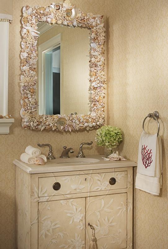 uno spazio neutro lavandino con una vanità materica, uno specchio rivestito di conchiglie e stelle marine, asciugamani stampati corallo