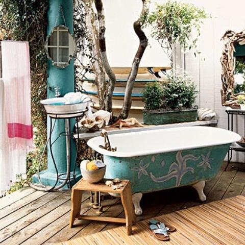 una vasca da bagno verniciata turchese, un pilastro turchese, uno sgabello con alcuni accessori