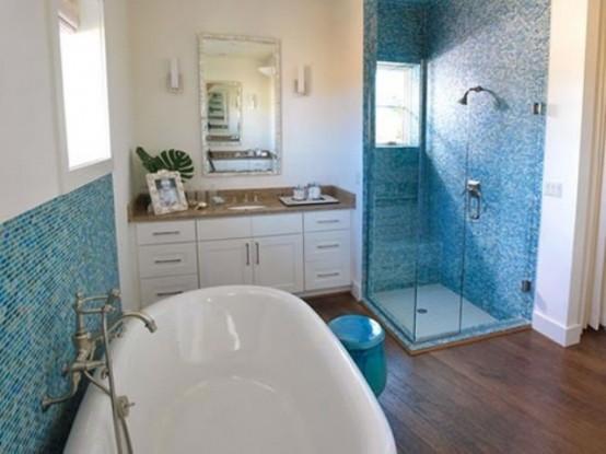 un bagno blu e bianco ispirato al mare con una vanità bianca con un piano di lavoro in legno, una vasca ovale