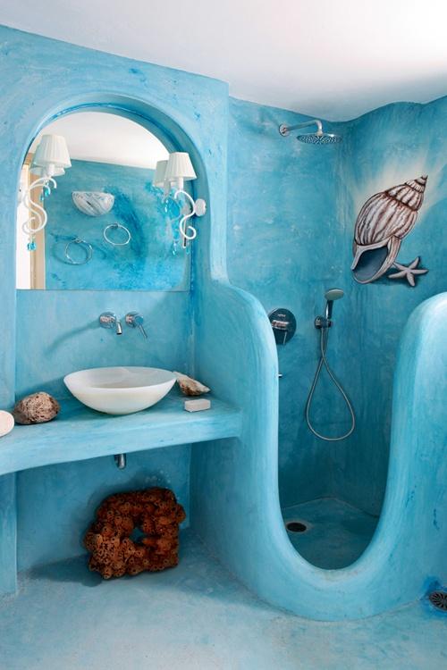 un bagno in gesso dipinto di blu con uno spazio doccia intagliato, lampade, pietre, coralli e una conchiglia dipinta