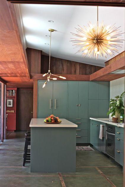 una cucina moderna verde della metà del secolo con lampade accattivanti e ripiani bianchi