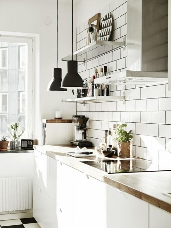 uno scandinavo bianco incontra la cucina moderna della metà del secolo con armadietti, blocco da macellaio, piastrelle bianche della metropolitana