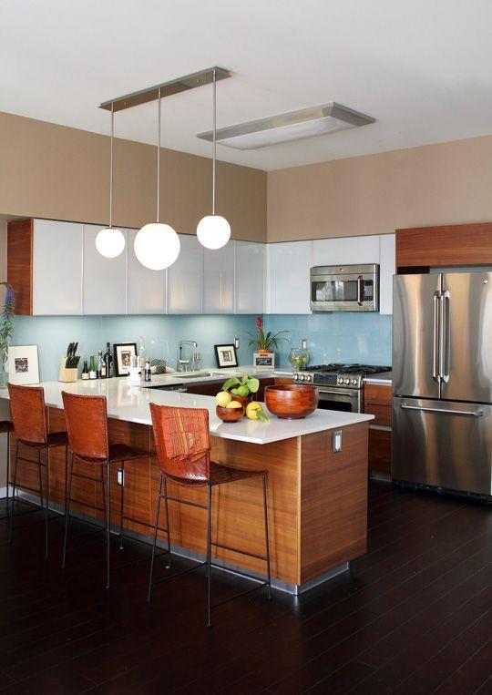 una cucina moderna della metà del secolo, dalle tinte ricche e bianche, con alzatina blu, elettrodomestici in metallo, lampade a sospensione