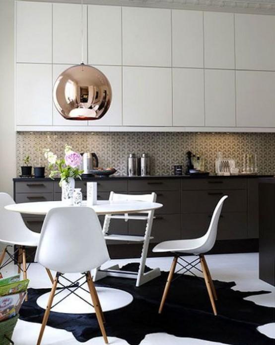 una cucina moderna della metà del secolo in bianco e nero con un set da pranzo bianco, un alzatina in mosaico e una grande lampada in rame