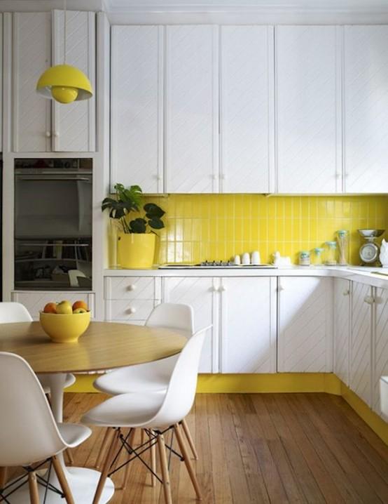 una cucina moderna della metà del secolo dalla struttura bianca con un backsplash giallo brillante, una lampada e pentole abbinate, sedie bianche