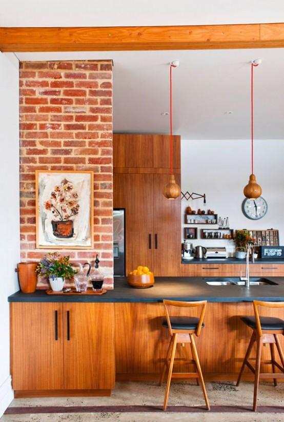 una luminosa cucina moderna della metà del secolo con mobili rossastri, lampade a sospensione, ripiani neri e opere d'arte