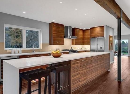 una cucina moderna di metà secolo ricca di macchie e bianche con una grande isola cucina con uno spazio per mangiare