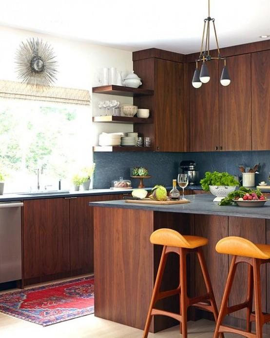 una cucina moderna della metà del secolo in legno tinto ricco con alzatina in pietra grigia, sgabelli arancioni, lampade a sospensione