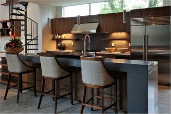 un'isola da cucina in legno tinto con elettrodomestici in metallo, un piano rialzato per mangiare e comodi sgabelli