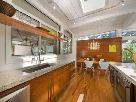 una cucina moderna della metà del secolo, armadi in legno e ripiani in pietra, alzatina con finestra e lucernari per una luce più naturale