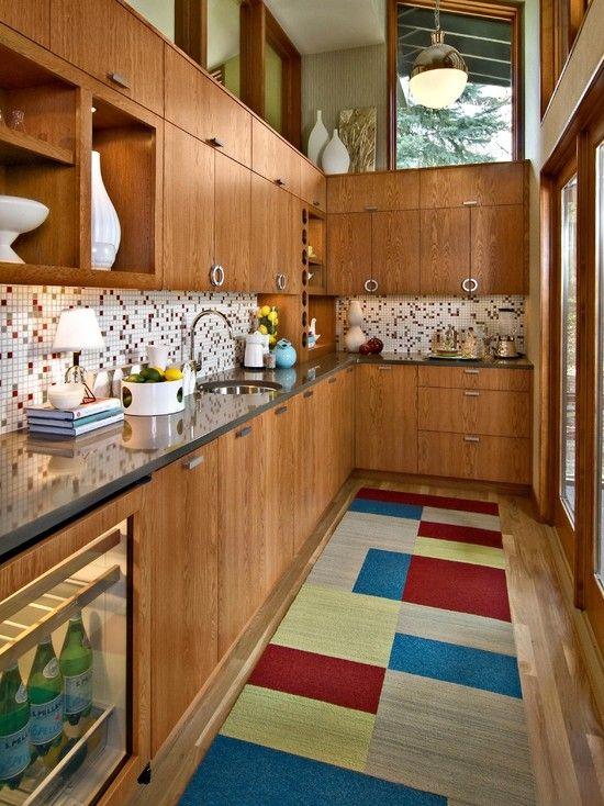 una cucina ricca di tinte con un backsplash di piastrelle a mosaico, un tappeto a blocchi di colore brillante e lucernari