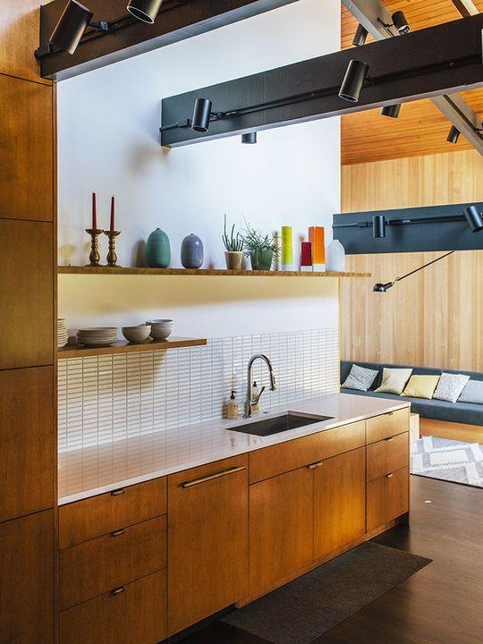 un moderno della metà del secolo incontra una cucina contemporanea con armadi in legno di colore chiaro, alzatina in piastrelle bianche, travi scure