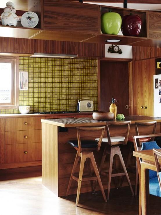 un'audace cucina moderna della metà del secolo con armadi ricchi di tinte, un backsplash in piastrelle gialle e armadi superiori sopra l'isola della cucina