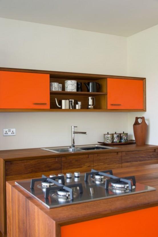 una cucina moderna della metà del secolo con legno ricco di tinte e armadi arancioni brillanti, elettrodomestici in metallo