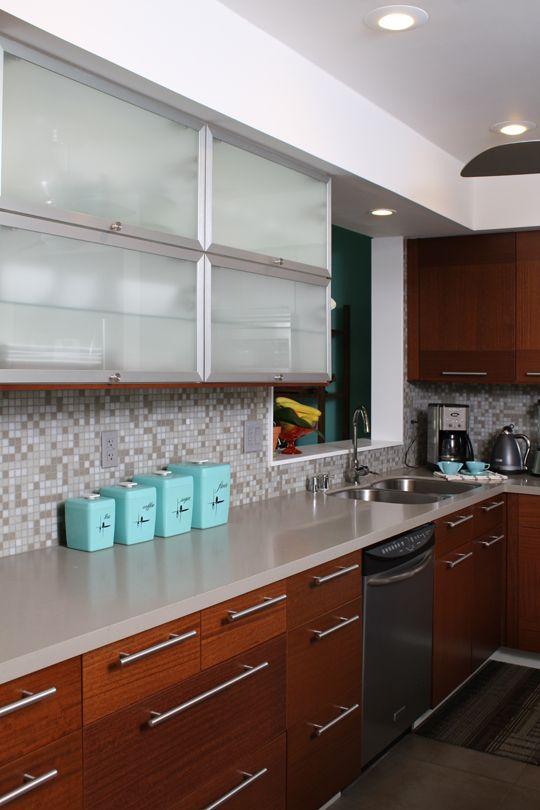 una cucina moderna della metà del secolo con vetro smerigliato e armadi in legno, un piano di lavoro neutro e alzatina in mosaico