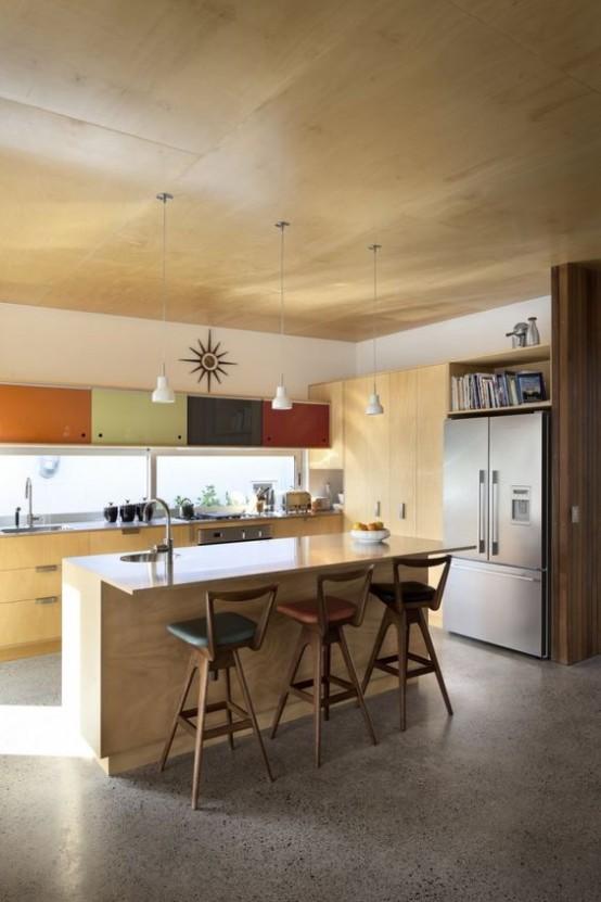 una cucina moderna della metà del secolo in compensato di colore chiaro con armadi dai colori tenui, lampade a sospensione e sgabelli