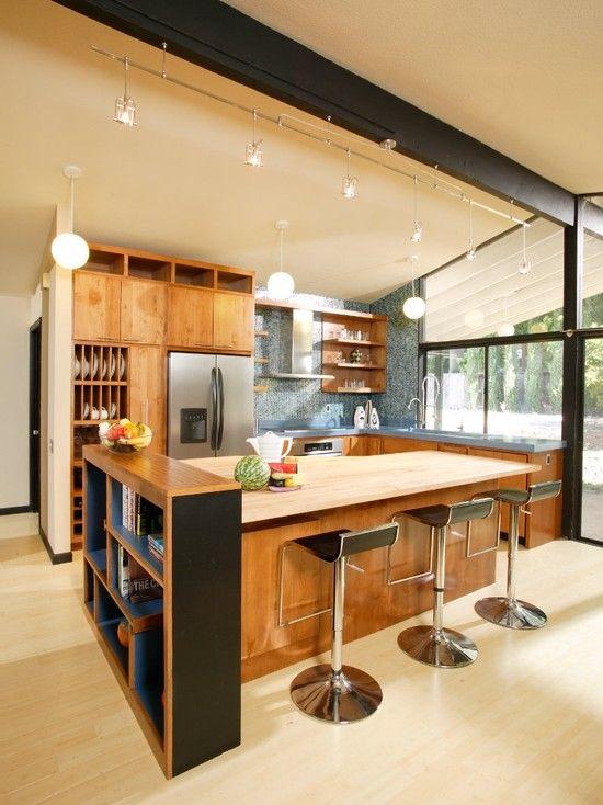 una cucina moderna della metà del secolo color latticello con armadi colorati, alzatina in piastrelle blu, sgabelli neri e lampade a sospensione