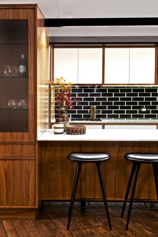 una cucina moderna della metà del secolo con una grande isola cucina in legno con un piano di lavoro bianco, sgabelli neri, un backsplash in piastrelle nere