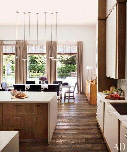 una cucina moderna della metà del secolo bianca e ricca di tinte con piano lavoro neutri e pavimenti in legno