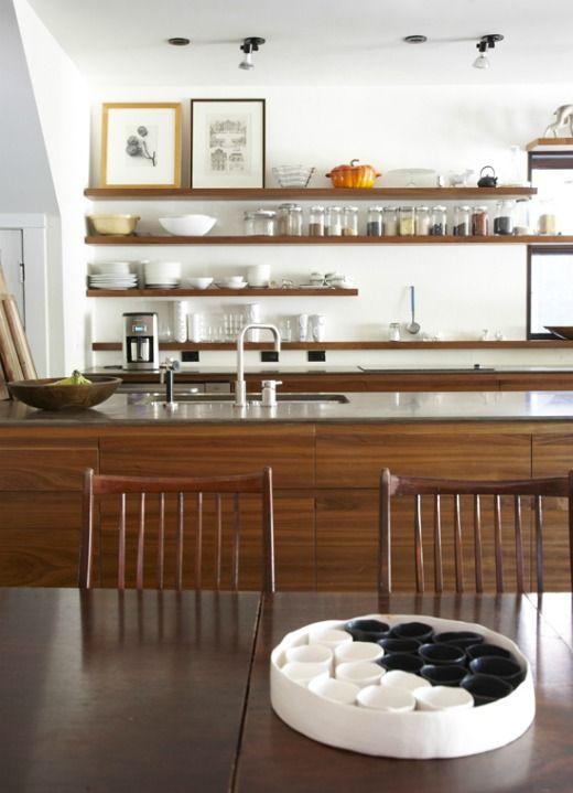 una cucina moderna della metà del secolo senza tomaie, scaffali aperti, una grande isola della cucina e opere d'arte
