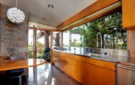 una moderna cucina in legno arancione della metà del secolo con ripiani in metallo, alzatina per finestra e tavolo abbinato