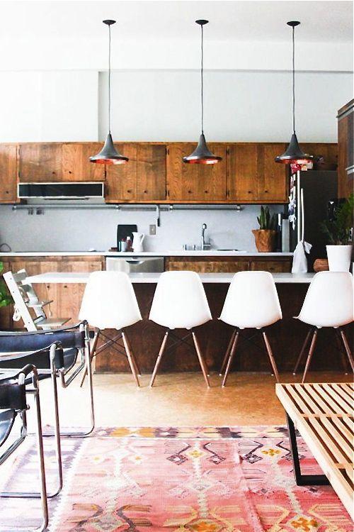 una cucina moderna della metà del secolo ricca di tinteggiate e bianche, sedie bianche e lampade a sospensione