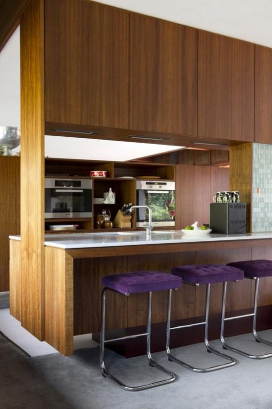 un contemporaneo incontra la cucina moderna della metà del secolo con armadi riccamente colorati, ripiani bianchi e sgabelli imbottiti viola