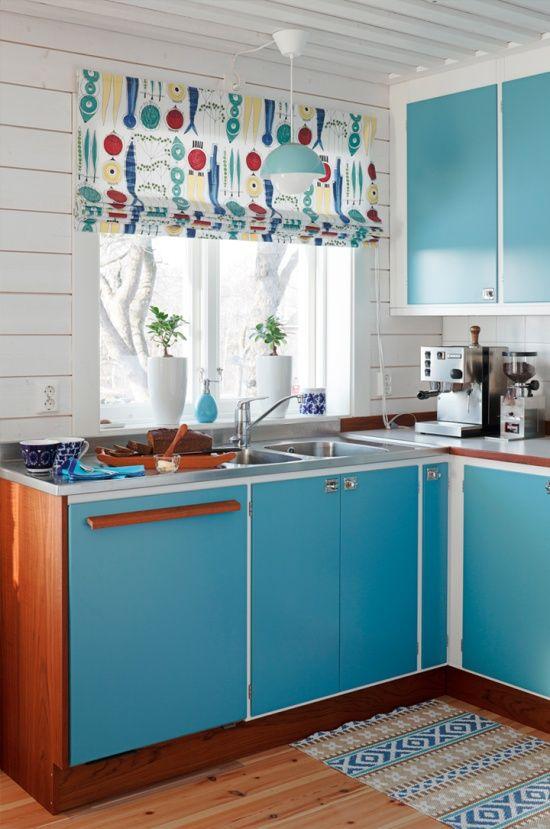 una cucina moderna blu brillante della metà del secolo con sfumature romane colorate, tocchi di ricco legno tinto
